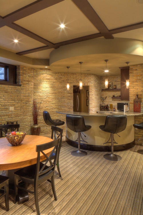 Basement with bar topped with brown stone countertop